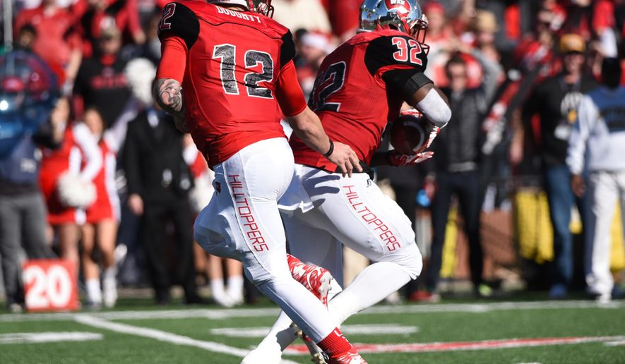Western Kentucky quarterback Brandon Doughty (12) hands the ball off to running back D'Andre Ferby (32) in the first half against Southern Mississippi in a NCAA college football game on Saturday, Dec. 5, 2015, at L.T. Smith Stadium in Bowling Green, Ky. (AP Photo/Michael Noble Jr.)