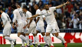 Real Madrid's Karim Benzema, right, celebrates with teammates after scoring the opening goal against Getafe during the Spanish La Liga soccer match between Real Madrid and Getafe at the Santiago Bernabeu stadium in Madrid, Saturday, Dec. 5, 2015. (AP Photo/Francisco Seco)