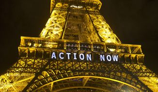 """The Eiffel Tower lights up Sunday with the slogan """"Action Now"""" for the COP 21, United Nations Climate Change Conference in Paris. Negotiators adopted a draft climate agreement Saturday that was cluttered with brackets and competing options, leaving ministers with the job of untangling key sticking points in what is envisioned to become a lasting, universal pact to fight global warming. (Associated Press)"""