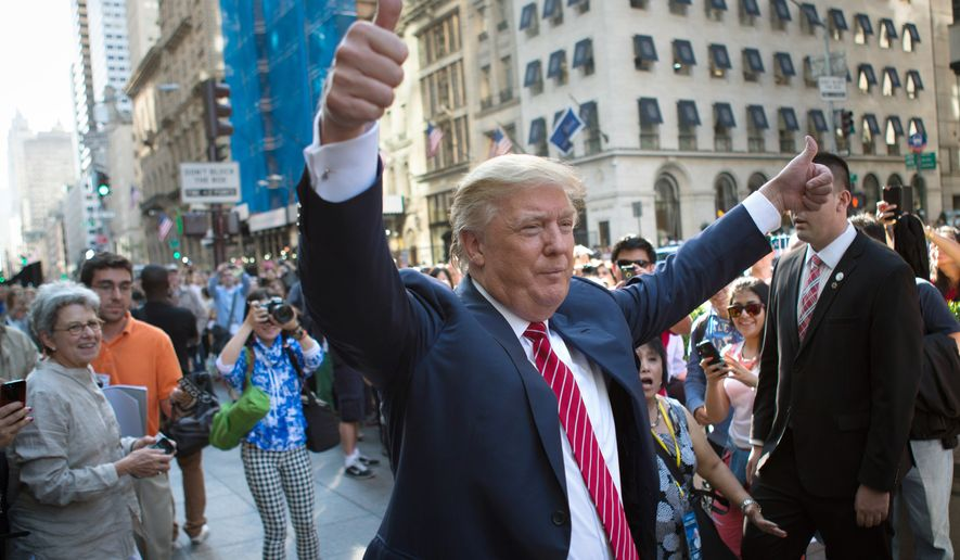 "In this Sept. 24, 2015, file photo, Republican presidential candidate Donald Trump waves to the crowd gathered in front of Trump Tower ahead of the arrival of the pope's motorcade for an appearance in New York's Central Park. Trump holds a trademark to use the words ""Central Park"" on items including furniture, chandeliers and even key chains. Records show his first application came in 1991, when the city's crime rate was near its height and the park had a less-than-glamorous reputation. (AP Photo/Kevin Hagen, File)"