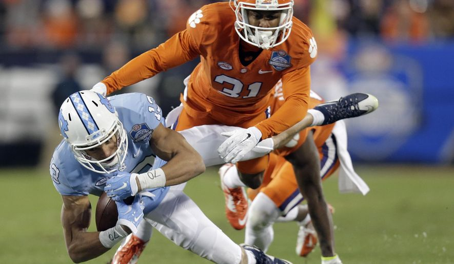 Clemson's Ryan Carter (31) moves in to tackle North Carolina's Mack Hollins (13) during the half of the Atlantic Coast Conference championship NCAA college football game in Charlotte, N.C., Saturday, Dec. 5, 2015. (AP Photo/Gerry Broome)