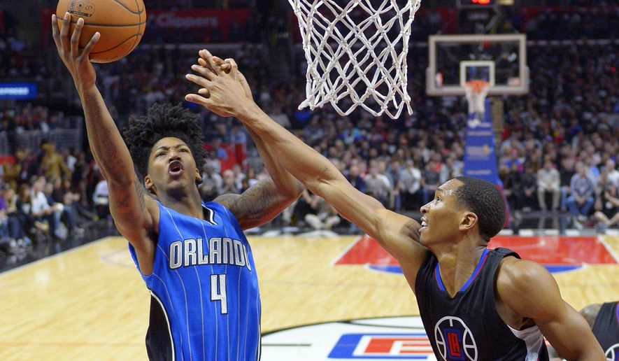 Orlando Magic guard Elfrid Payton, left, shoots as Los Angeles Clippers forward Wesley Johnson defends during the first half of an NBA basketball game, Saturday, Dec. 5, 2015, in Los Angeles. (AP Photo/Mark J. Terrill)