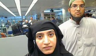 This July 27, 2014, file photo provided by U.S. Customs and Border Protection shows Tashfeen Malik, left, and Syed Farook, as they passed through O'Hare International Airport in Chicago. The husband and wife died on Dec. 2, 2015, in a gun battle with authorities several hours after their assault on a gathering of Farook's colleagues in San Bernardino, Calif. (U.S. Customs and Border Protection via AP)