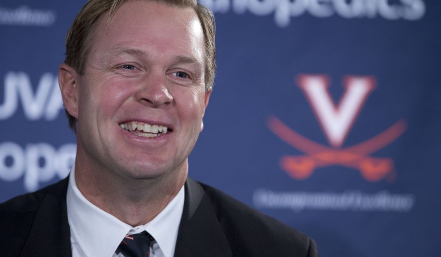 New University of Virginia NCAA college head football coach, Bronco Mendenhall, smiles during a news conference at the school  in Charlottesville, Va., Monday, Dec. 7, 2015.  Mendenhall takes over after his current team Brigham Young University competes in it's bowl game. (AP Photo/Steve Helber)