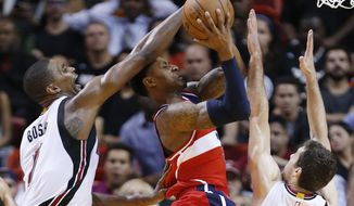 Washington Wizards guard Bradley Beal, center, goes up for a shot against Miami Heat forward Chris Bosh (1) and guard Goran Dragic, right, during the second half of an NBA basketball game, Monday, Dec. 7, 2015, in Miami. The Wizards defeated the Heat 114-103. (AP Photo/Wilfredo Lee)