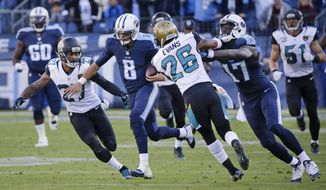 Tennessee Titans quarterback Marcus Mariota (8) gets past Jacksonville Jaguars defenders Dwayne Gratz (27) and Josh Evans (26) as Titans wide receiver Dorial Green-Beckham (17) blocks as Mariota runs 87 yards for a touchdown in the second half of an NFL football game Sunday, Dec. 6, 2015, in Nashville, Tenn. (AP Photo/James Kenney)