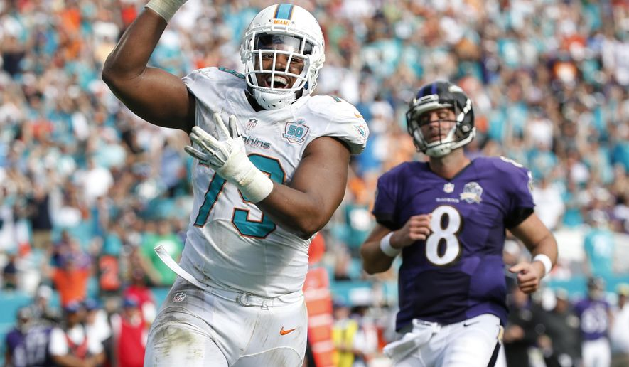 Miami Dolphins defensive end Derrick Shelby (79) smiles as he scores a touchdown after intercepting the ball during the first half of an NFL football game against the Baltimore Ravens, Sunday, Dec. 6, 2015, in Miami Gardens, Fla. Baltimore Ravens quarterback Matt Schaub (8) is running behind Shelby.  (AP Photo/Wilfredo Lee)