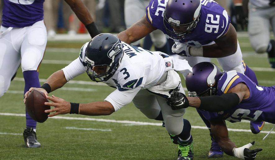 Seattle Seahawks quarterback Russell Wilson (3) dives for a eight-yard touchdown run as Minnesota Vikings cornerback Antone Exum (32) defensive tackle Tom Johnson (92) try to bring him down in the first half of an NFL football game Sunday, Dec. 6, 2015 in Minneapolis. (AP Photo/Ann Heisenfelt)