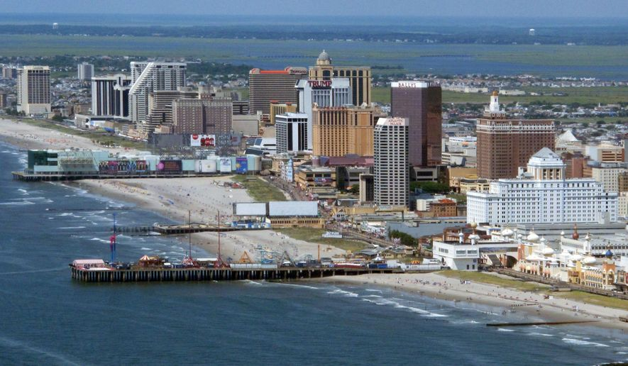This July 11, 2014, aerial photo, shows the Atlantic City, N.J., beachfront with many of its Boardwalk casinos. Nearly a month after Gov. Chris Christie vetoed most of a financial aid package for the struggling gambling resort, no agreement has been reached on how to help the city, which continues to suffer from the shrinking of its casino market. (AP Photo/Wayne Parry)
