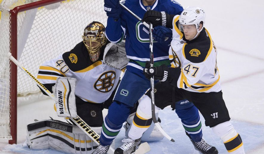 Boston Bruins defenseman Torey Krug (47) tries to clear Vancouver Canucks right wing Adam Cracknell (24) from in front of Boston Bruins goalie Tuukka Rask (40) during the first period of an NHL hockey game Saturday, Dec. 5, 2015, in Vancouver, British Columbia. (Jonathan Hayward/The Canadian Press via AP)