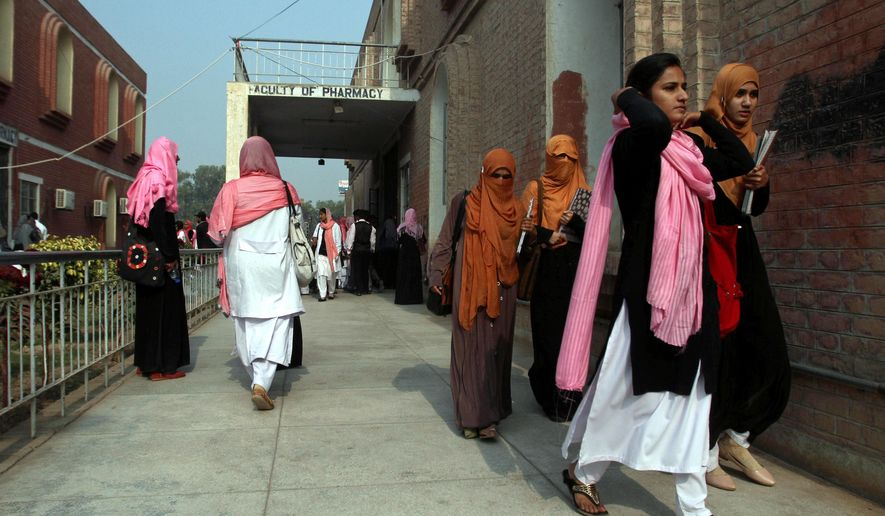 Students leave the Pharmacy department at Bahauddin Zakariya University in Multan, Pakistan, Monday, Dec. 7, 2015. Pakistani intelligence officials say the California shooter Tashfeen Malik attended a religious school while living in Multan where she studied pharmacy. The officials identified the school on Monday as the Al-Huda International Seminary, a women-only madrassa with a chain across Pakistan and branches in the U.S. and Canada. (AP Photo/Asim Tanveer)