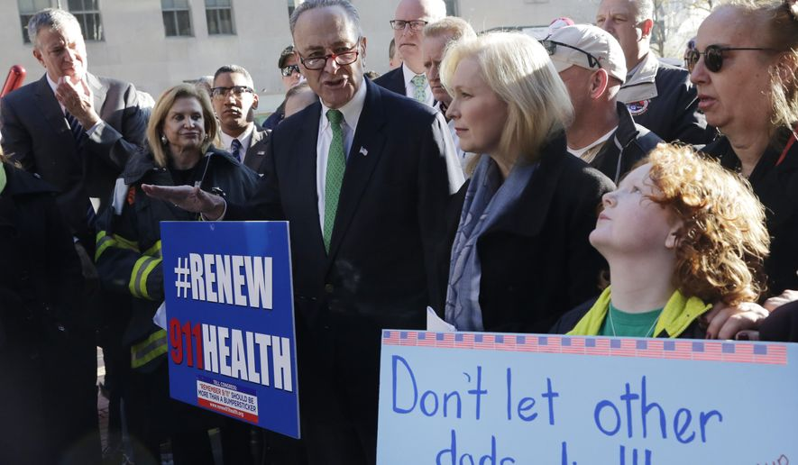 CORRECTS SPELLING OF GILLIBRAND - Jack McNamara, 9, right, holds a sign on behalf of his late father during a rally calling for the funding of the Zadroga Act, Sunday, Dec. 6, 2015, in New York. John McNamara, who served in the New York Fire Department, worked at the World Trade Center site following the attacks of Sept. 11, 2001 and died in 2009 of cancer. Sen. Charles Schumer, D-NY, center, Sen. Kirsten Gillibrand, D-NY, second right, and other officials joined in the rally. The Act, which funds medical care for 9/11 first-responders, is set to expire and was not included in the Transportation Bill that passed the Senate earlier this week. (AP Photo/Mark Lennihan)