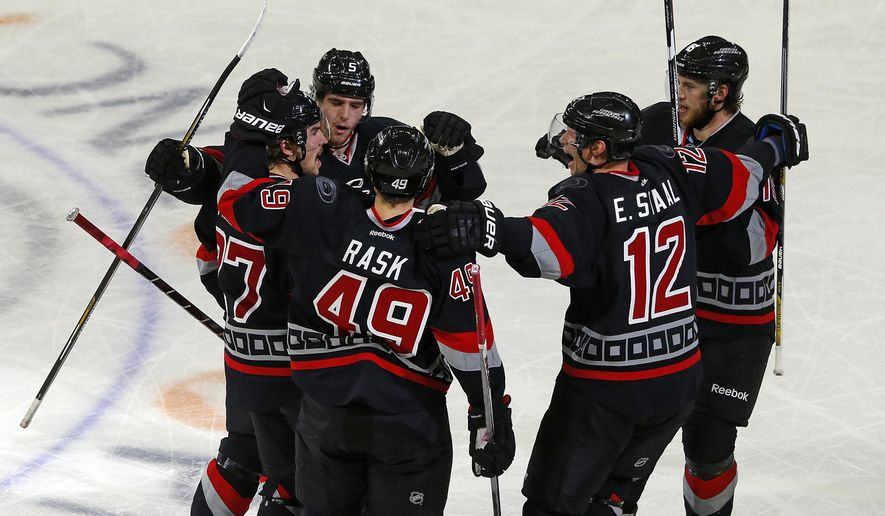 Carolina Hurricanes' Justin Faulk, left, is congratulated on his go ahead goal by teammates Noah Hanifin (5), Victor Rask (49), Eric Staal (12), and Elias Lindholm (16) of Sweden during closing minutes of the third period of an NHL hockey game against the Arizona Coyotes, Sunday, Dec. 6, 2015, in Raleigh, N.C. The Hurricanes won 5-4. (AP Photo/Karl B DeBlaker)