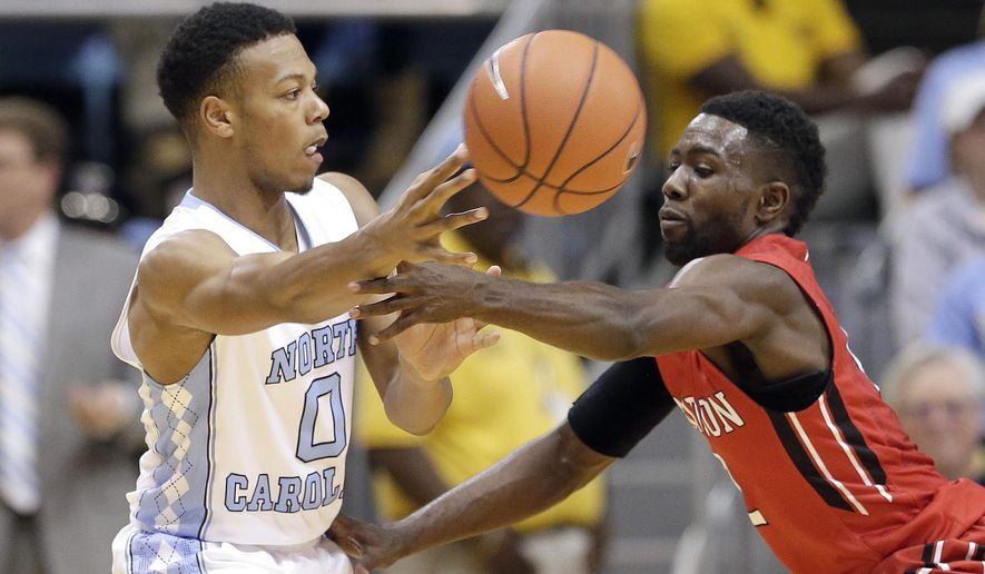 North Carolina's Nate Britt (0) passes as Davidson's Jordan Watkins defends during the second half of an NCAA college basketball game in Chapel Hill, N.C., Sunday, Dec. 6, 2015. North Carolina won 98-65. (AP Photo/Gerry Broome)