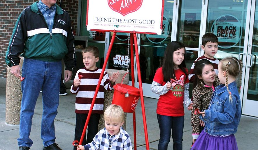 In this photo taken on Nov. 27, 2015, Rob Francis, left, rings the bells for the Salvation Army with his six grandchildren in Ashland, Kentucky. This was his second year of ringing the bells. (Adam Black /The Daily Independent via AP) MANDATORY CREDIT
