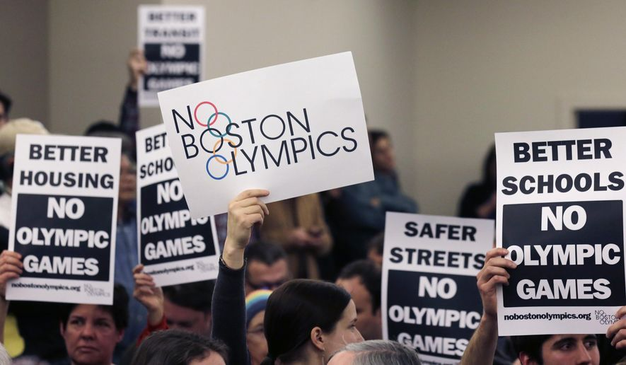"""FILE - In this Feb. 5, 2015, file photo, people hold up placards against the Olympic Games coming to Boston, during the first public forum regarding the city's 2024 Olympic bid, in Boston. Activists from """"No Boston Olympics"""" stirred up so much spirited opposition to the 2024 Games, the U.S. Olympic Committee yanked Boston as its bid city. Since then, the group has been exporting its best practices for fomenting resistance, working with Olympics opponents as far away as Los Angeles and Hamburg, Germany. (AP Photo/Charles Krupa, File)"""