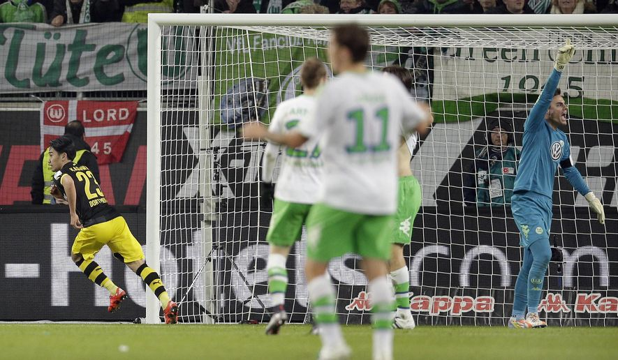 Dortmund's Shinji Kagawa, left, celebrates after scoring his side's second goal during the German Bundesliga soccer match between VfL Wolfsburg and Borussia Dortmund in Wolfsburg, Germany, Saturday, Dec. 5, 2015. (AP Photo/Michael Sohn)