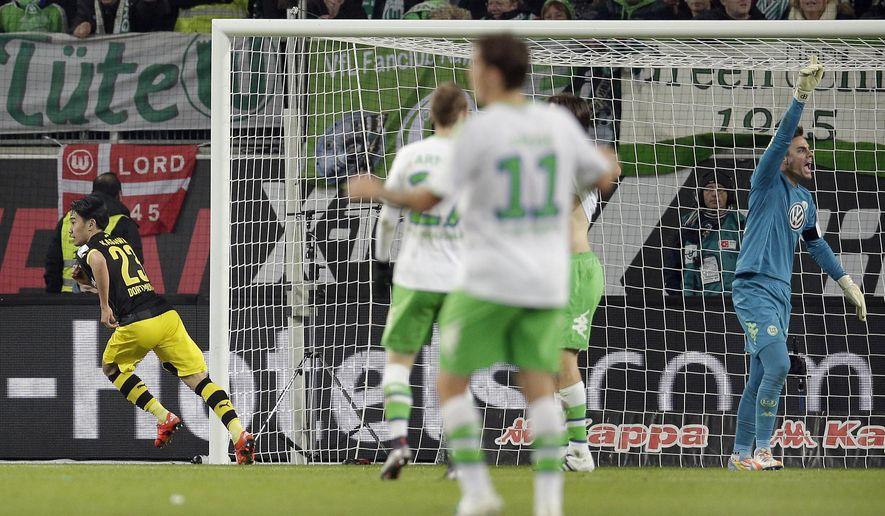 Dortmund's Shinji Kagawa, left, celebrates after scoring his side's second goal during the German Bundesliga soccer match between VfL Wolfsburg and Borussia Dortmund in Wolfsburg, Germany, Saturday, Dec. 5, 2015. (AP Photo/Michael Sohn)