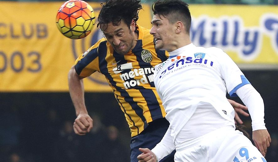 Hellas Verona's Luca Toni, left, heads the ball past Empoli's Federico Barba during their Serie A soccer match at the Bentegodi stadium in Verona, Italy, Sunday, Dec. 6, 2015. World Cup winner Luca Toni has hinted he could retire at the end of the season. Toni, who scored 16 goals in 47 international appearances, won the World Cup with Italy in 2006. (Filippo Venezia/ANSA via AP)