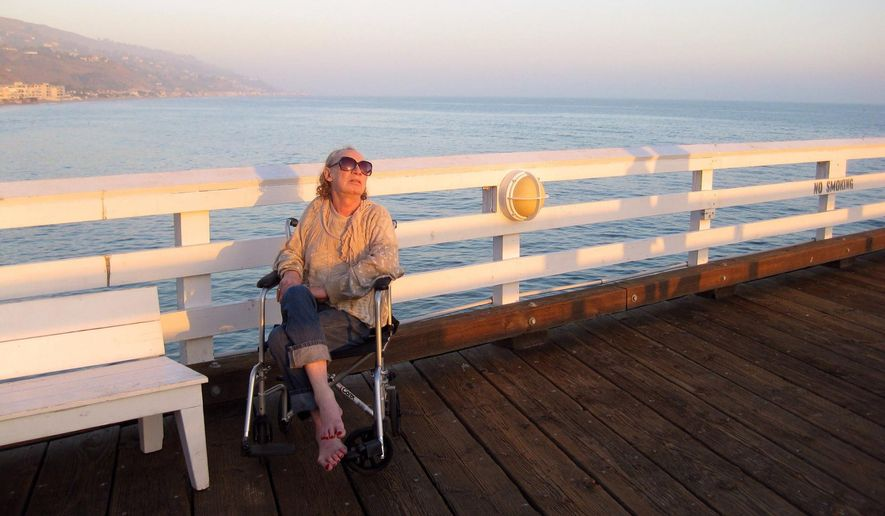 """In this 2012 photo provided by David Chick, actress Holly Woodlawn sits on Fisherman's Pier in Malibu, Calif. Woodlawn, who starred in the 1970 Paul Morrissey film """"Trash"""" and was immortalized in the first few lines of Lou Reed's """"Walk on the Wild Side,"""" died Sunday, Dec. 6, 2015, in Los Angeles after a battle with cancer. She was 69. (David Chick via AP)"""