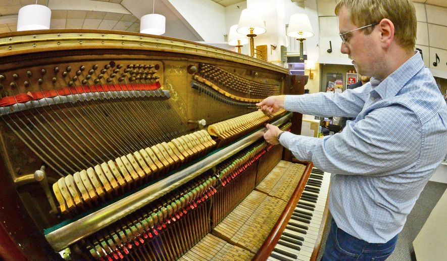ADVANCE FOR MONDAY DEC. 7 AND THEREAFTER - This Wednesday Nov. 25, 2015 photo shows Jonathan Cleghorn as he works on a 19th century piano at the Kanawha Piano Gallery in Clendenin, W.Va. Cleghorn is trying to raise money for a second trip to the town of Urubamba, in Peru, to continue restoring a unique piano from the late 1800s. (Tom Hindman/Charleston Gazette-Mail via AP)