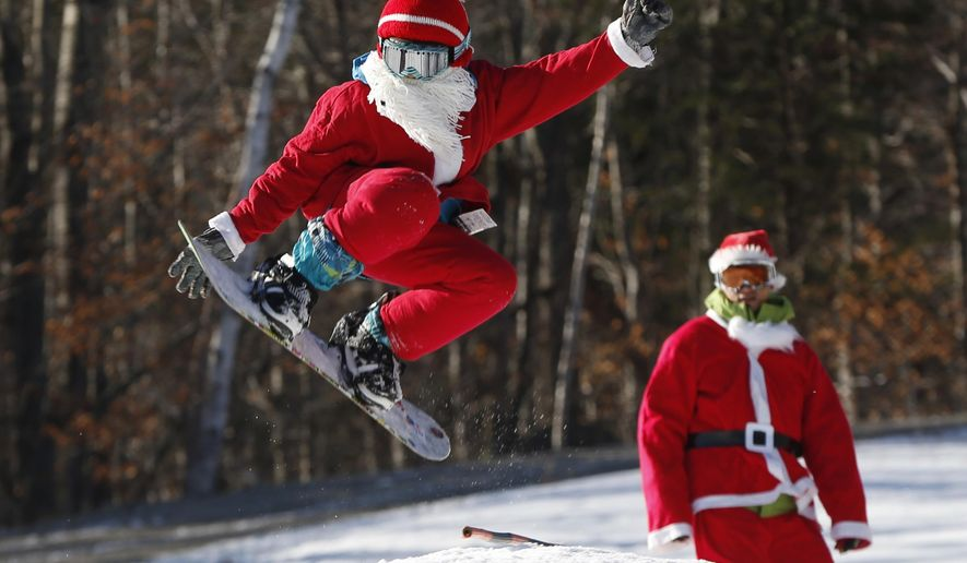 Snowboarder Jaden Bao, 12, of South Portland, Maine, catches some air while participating in Santa Sunday, the 16th annual charity fundraising event at the Sunday River ski resort, Sunday, Dec. 6, 2015, in Newry, Maine. (AP Photo/Robert F. Bukaty)
