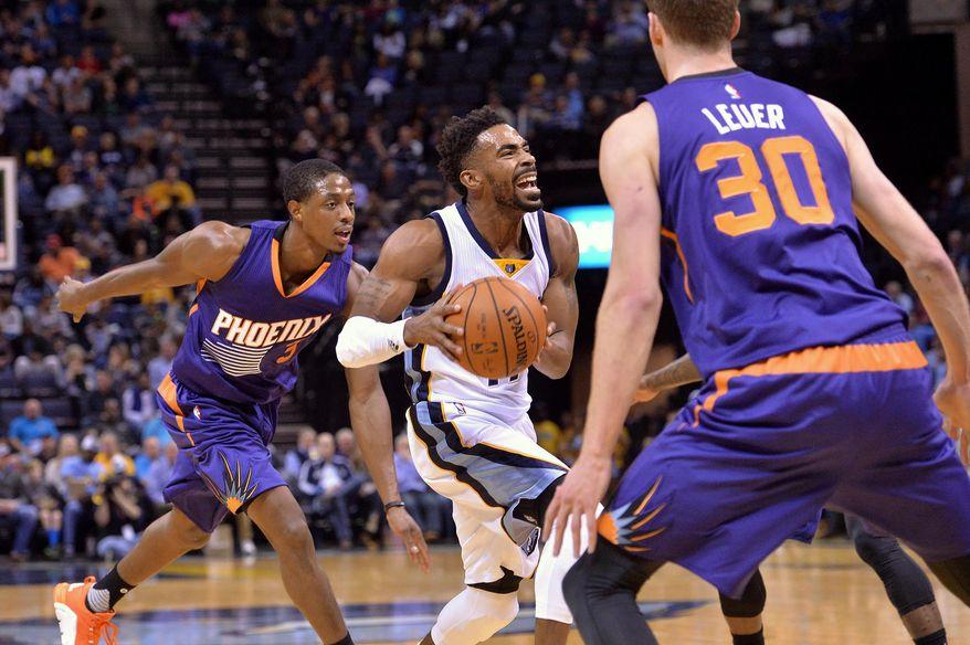 Memphis Grizzlies guard Mike Conley, center, drives between Phoenix Suns guard Brandon Knight (3) and forward Jon Leuer (30) in the first half of an NBA basketball game Sunday, Dec. 6, 2015, in Memphis, Tenn. (AP Photo/Brandon Dill)