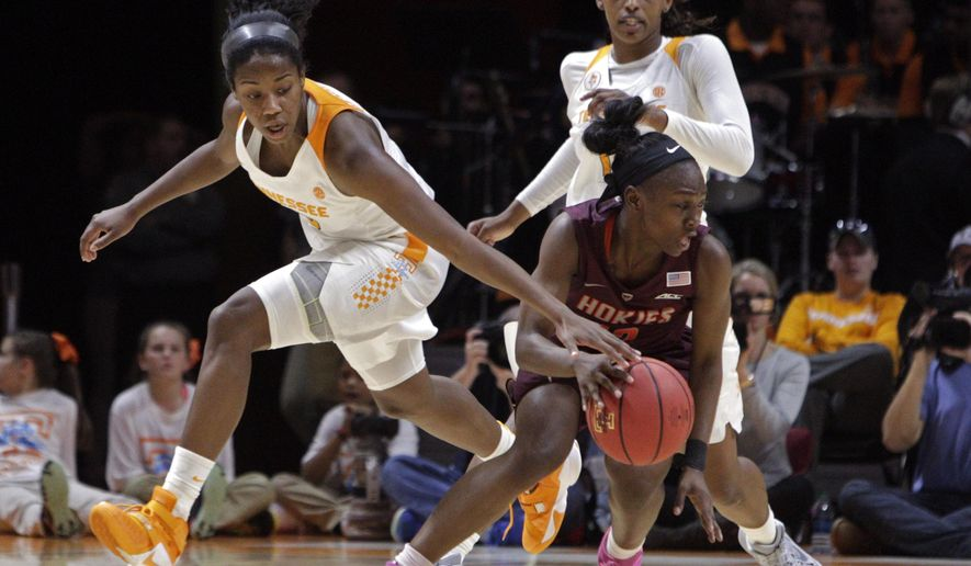 Tennessee guard Meme Jackson, left, attempts to steal the ball from Virginia Tech guard Chanette Hicks, front right, as Tennessee's Bashaara Graves, back right, looks ons in the first half of an NCAA college basketball game Sunday, Dec. 6, 2015, in Knoxville, Tenn. (AP Photo/Wade Payne)