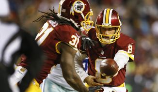 Washington Redskins quarterback Kirk Cousins (8) hands off the ball to Washington Redskins running back Matt Jones (31) during the first half of an NFL football game against the Dallas Cowboys in Landover, Md., Monday, Dec. 7, 2015. (AP Photo/Patrick Semansky)