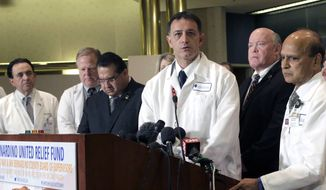 Dr. Michael Neeki, center at podium, an emergency room doctor who doubles as a member of the local SWAT team, with Dr. Dev GnanaDev, second from right,  chief of surgery at Arrowhead Regional Medical Center, comments on the victims of  the San Bernardino shootings at a news conference in San San Bernardino, Calif., on Monday, Dec. 7, 2015. (AP Photo/Nick Ut)