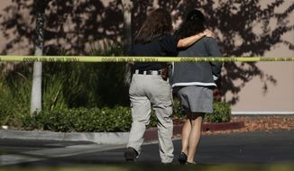 An unidentified woman, right, is comforted by an investigator at the Inland Regional Center, the site of last week's shooting rampage that killed 14 people, Tuesday, Dec. 8, 2015, in San Bernardino, Calif. Just days before Syed Farook carried out the attack that killed 14 people, Farook practiced with a rifle during one of several recent visits to a local shooting range, authorities said. Sometimes he was joined by his wife, his partner in the attack. (AP Photo/Jae C. Hong)