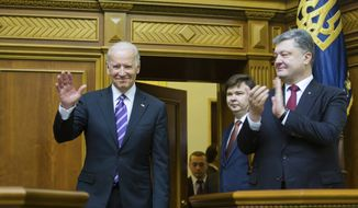 Ukrainian President Petro Poroshenko, right, applauds to U.S. Vice President Joe Biden, left, after he addressed the Ukraine Parliament in Kiev, Ukraine, Tuesday, Dec. 8, 2015. Biden addressed the Ukrainian parliament on Tuesday, criticizing Russia and saying that the US and all of Europe stood with Ukraine. (AP Photo/Mikhail Palinchak, Pool)