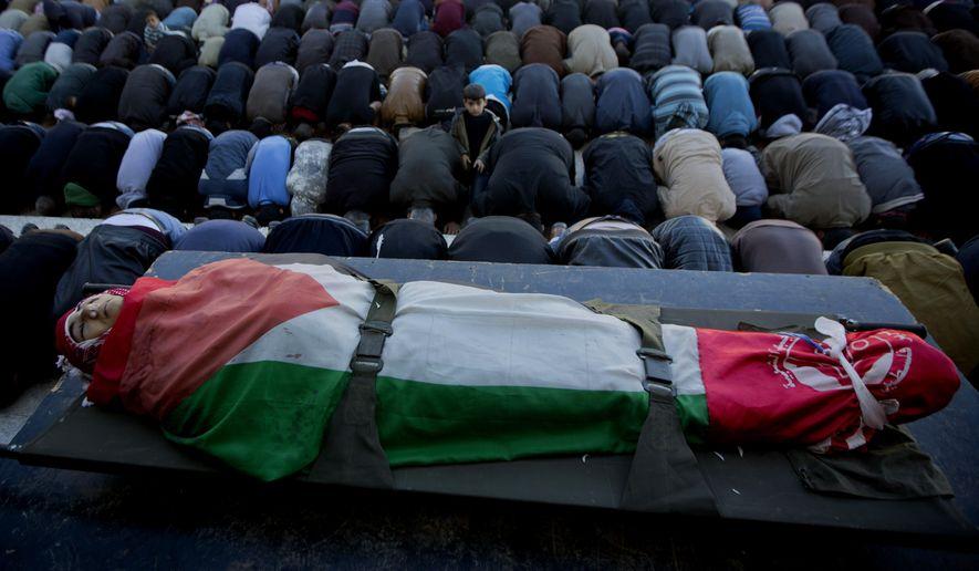 Palestinians offer the funeral prayers over the body of Malik Shaheen, 21, who was killed in clashes with Israeli troops, during his funeral in Deheishe Refugee Camp, near the West Bank city of Bethlehem, Tuesday, Dec. 8, 2015. (AP Photo/Majdi Mohammed)