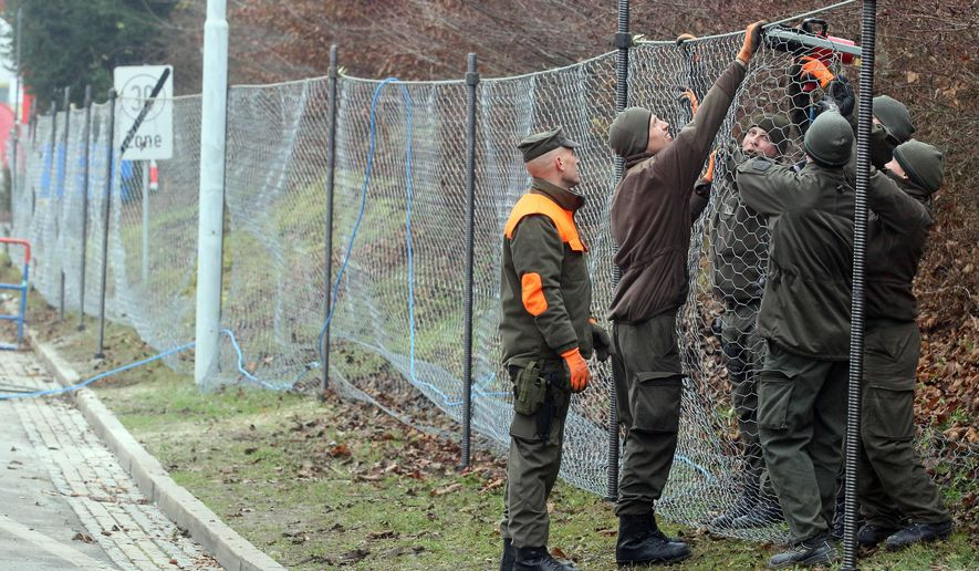 Austrian soldiers are building a fence to improve the procedure for arriving refugees at the border between Slovenian and Austria in Spielfeld, Austria, Tuesday, Dec. 8, 2015. (AP Photo/Ronald Zak)