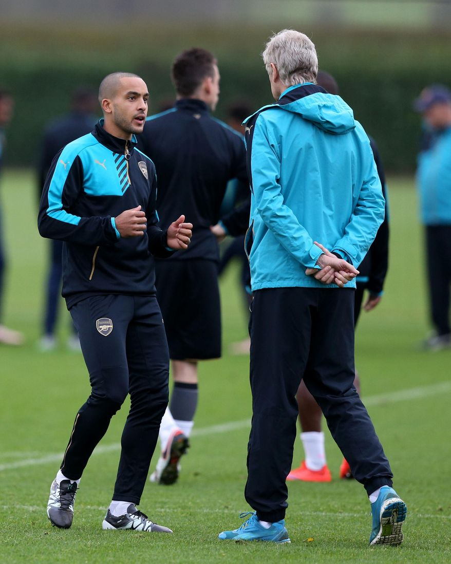 Arsenal manager Arsene Wenger, right, speaks to Theo Walcott during a training session at London Colney, London Tuesday Dec. 8, 2015.  (Simon Cooper/PA via AP) UNITED KINGDOM OUT