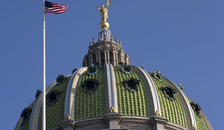 The United States flag waves in the wind at the Pennsylvania Capitol building Tuesday, Dec. 8, 2015, in Harrisburg, Pa. The Pennsylvania House and Senate moved toward a showdown over competing spending and tax plans Monday, with the fate of suffering counties, schools and social services agencies hanging in the balance of a 5-month budget stalemate. (AP Photo/Matt Rourke)