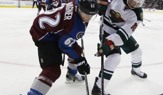 Colorado Avalanche right wing Chris Wagner, left, fights for control of the puck with Minnesota Wild center Ryan Carter in the second period of an NHL hockey game, Monday, Dec. 7, 2015, in Denver. (AP Photo/David Zalubowski)