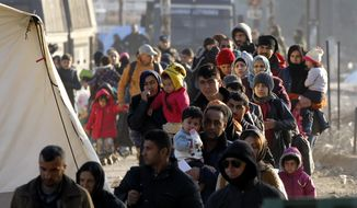 Refugees walk towards Macedonia after arriving at the refugee camp near Idomeni in northern Greece, by the border with Macedonia, photographed from the Macedonian side of the border, near the town of Gevgelija, on Wednesday, Dec. 9, 2015. Greek riot police have removed Wednesday hundreds of protesting migrants from a border crossing to Macedonia, which is denying them entry, deeming them to be economic migrants and not refugees. Macedonia, along with Serbia, Croatia and Slovenia, is turning away from its borders migrants who are not from war zones such as Syria, Afghanistan and Iraq. (AP Photo/Boris Grdanoski)