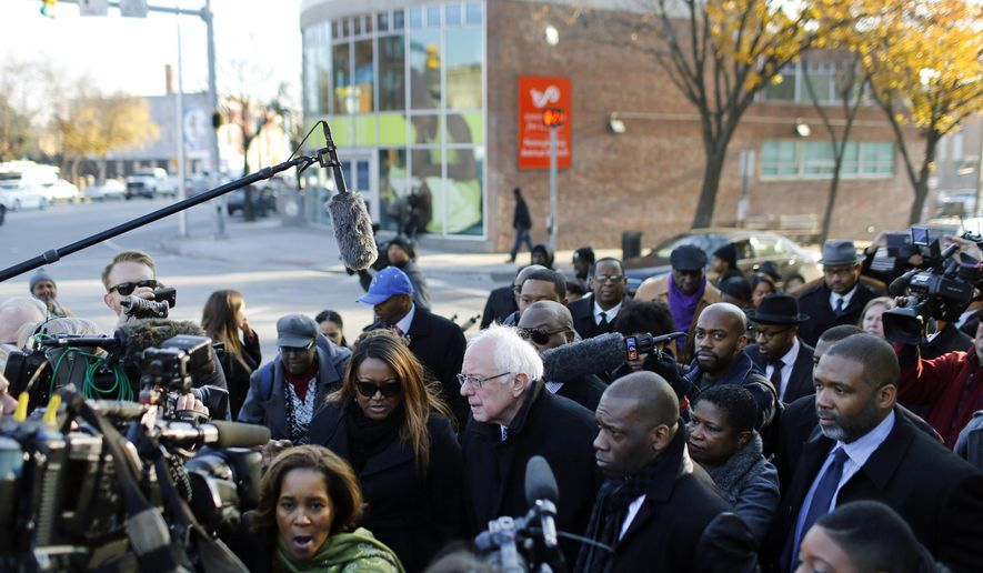 Democratic presidential candidate, Sen. Bernie Sanders, I-Vt., center, walks through the intersection of North and Pennsylvania Avenues, the site of unrest following the funeral of Freddie Gray, in Baltimore, Tuesday, Dec. 8, 2015. Sanders toured areas of unrest following Gray's funeral and met with African-American civic and religious leaders to discuss issues affecting the African-American community. (AP Photo/Patrick Semansky)