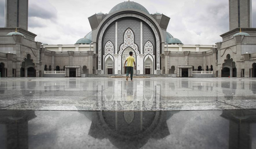 A Malaysian Muslim man walks towards a mosque for noon prayers in Kuala Lumpur, Malaysia, Tuesday, Dec. 8, 2015. Over 60 percent of Malaysia's population is Muslim, with Buddhism, Christianity and Hinduism comprising of the nation's other religions. (AP Photo/Joshua Paul)
