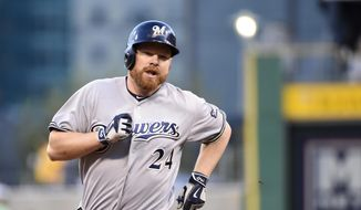 FILE - In this Sept. 11, 2015, file photo, Milwaukee Brewers' Adam Lind trots around the bases after hitting a homerun during a game against the Pittsburgh Pirates, in Pittsburgh. The busy Seattle Mariners have acquired first baseman Adam Lind from the Milwaukee Brewers for three young minor league pitchers. The team announced the trade Wednesday, Dec. 9, 2015,  at the winter meetings. (AP Photo/Fred Vuich, File) **FILE**