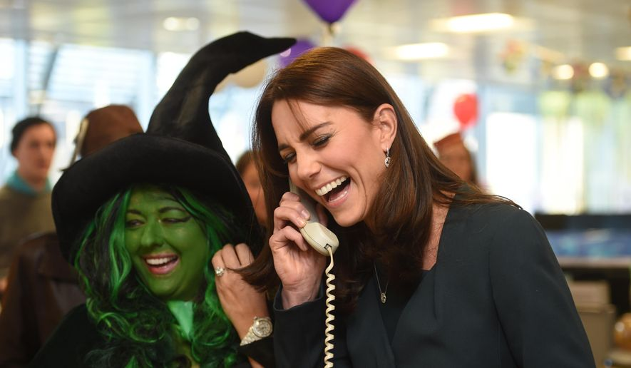 Kate Duchess of Cambridge laughs on the phone as a trader in fancy dress looks on  as the Duches attends ICAP's 23rd annual Charity Day in London Wednesday Dec. 9, 2015. The Duchess and Prince William  joined  ICAP' s brokers to raise revenues from trading on ICAP's charity day that will be donated to a range of charities, including SkillForce, of which William is patron, and SportsAid and Place2Be, of which Kate is patron.  (Jeremy Selwyn, Pool via AP)