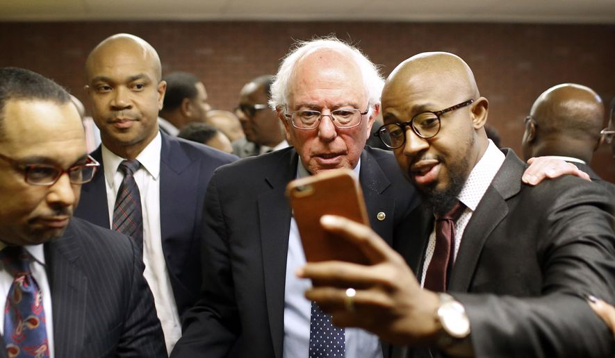 Democratic presidential candidate, Sen. Bernie Sanders, I-Vt., center, poses for a selfie with Rev. Carlton Lee at the Freddie Gray Empowerment Center in Baltimore, Tuesday, Dec. 8, 2015, after taking a walking tour of Gray's neighborhood and meeting with African-American civic and religious leaders in Baltimore, Tuesday, Dec. 8, 2015. (AP Photo/Patrick Semansky) ** FILE **