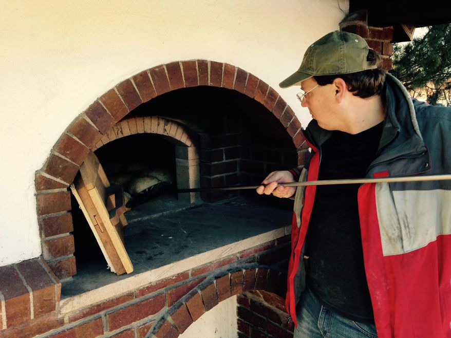 ADVANCE FOR USE SATURDAY, DEC. 12  - In this photo taken Nov. 21, 2015, Hamline Church member Mark Ireland arranges some loaves during a recent bread bake at the church's new community brick bread oven in St. Paul, Minn. (Richard Chin/Pioneer Press via AP)  MINNEAPOLIS STAR TRIBUNE OUT; MANDATORY CREDIT