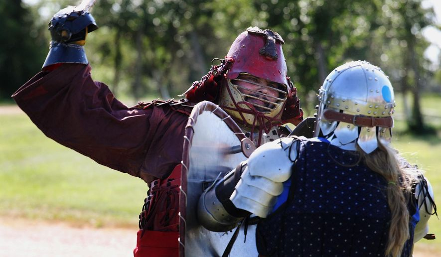 In a Saturday, Aug. 1, 2015 photo, Jeremy Mallory, Mosinee, left, and Terri Harteau demonstrate their fighting skills at Harteau's home in Stratford, Wisc. Mallory and Harteau are members of the Society for Creative Anachronism, which is hosting a Middles Ages festival this weekend in Wisconsin Rapids. (Dan Young/Appleton Post-Crescent via AP) /The Post-Crescent via AP) MANDATORY CREDIT