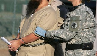 FILE - In this Dec. 6, 2006 file photo, reviewed by a U.S. Dept of Defense official, a shackled detainee is transported by a female guard, front, and male guard, behind, away from his annual Administrative Review Board hearing with U.S. officials, at Camp Delta detention center, Guantanamo Bay U.S. Naval Base, Cuba. A U.S. Army officer told a court on Tuesday, Dec. 8, 2015 that she started to use women to transport prisoners in 2014 due to a shortage of guards. A judge has issued a temporary ban the military is seeking to lift. Muslim prisoners say contact with unrelated females violates their religion. (AP Photo/Brennan Linsley, File)