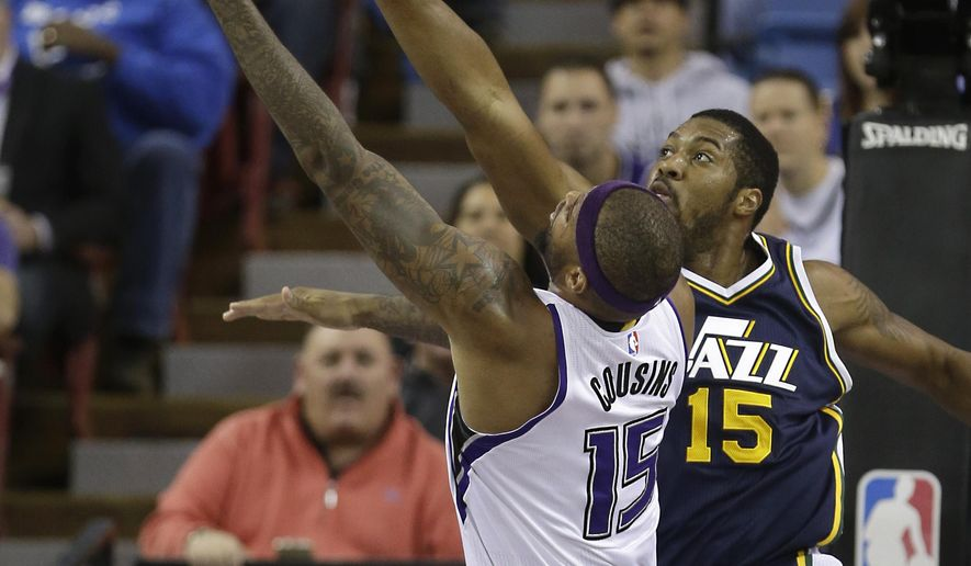 Sacramento Kings forward DeMarcus Cousins, left, goes to the basket against Utah Jazz forward Derrick Favors during the first quarter of an NBA basketball game in Sacramento, Calif., Tuesday, Dec. 8, 2015. (AP Photo/Rich Pedroncelli)