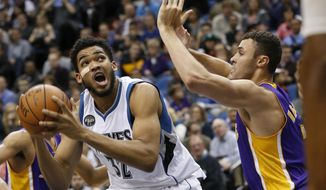 Minnesota Timberwolves center Karl-Anthony Towns (32) drives against Los Angeles Lakers forward Larry Nance Jr., right,  during the first half of an NBA basketball game in Minneapolis, Wednesday, Dec. 9, 2015. (AP Photo/Ann Heisenfelt)