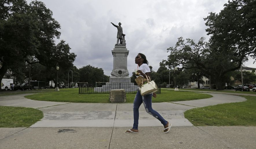 In this Sept. 2, 2015 photo, a woman walks past a monument of Jefferson Davis on Jefferson Davis Parkway at Canal Street in New Orleans. (AP Photo/Gerald Herbert)