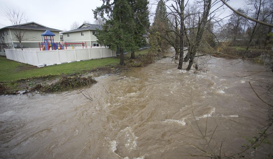 Johnson Creek swells near flood stage in Portland, Ore., as the Pacific Northwest was soaked by another night of heavy rain, Wednesday, Dec. 9, 2015. The Oregon Department of Transportation says landslides and high water have closed parts of many state highways.  (AP Photo/Steve Dipaola)